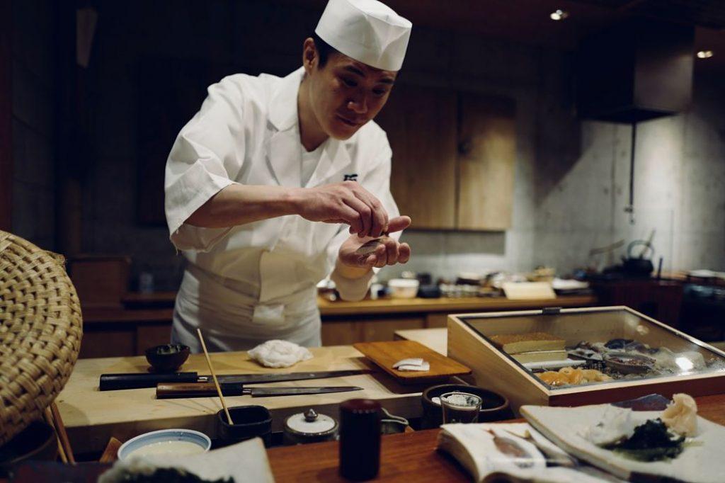 Cocinero japonés elaborando sushi a mano.