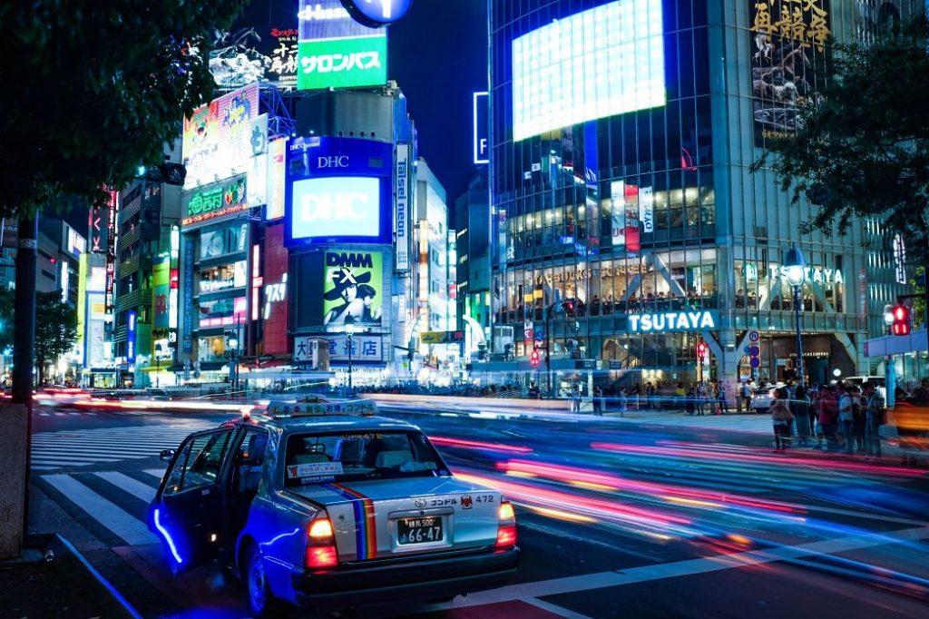 Taxi de noche con los neones del barrio de Shibuya, Tokio, al fondo