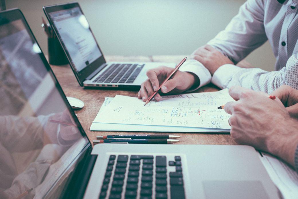 Trabajador en oficina con portátil y documentos