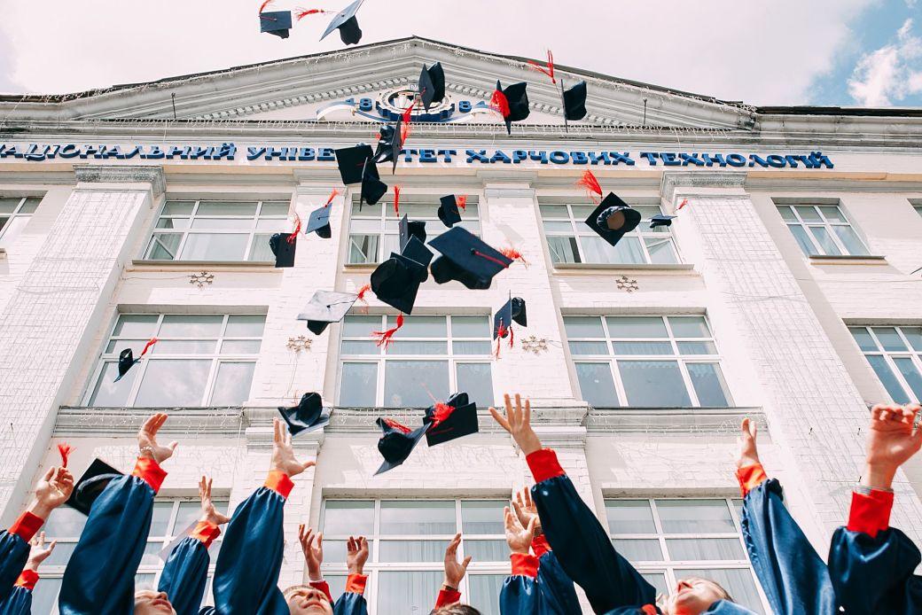 Estudiantes universitarios lanzando el birrete