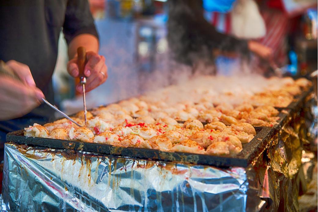 Plancha de takoyaki en puesto de comida callejera