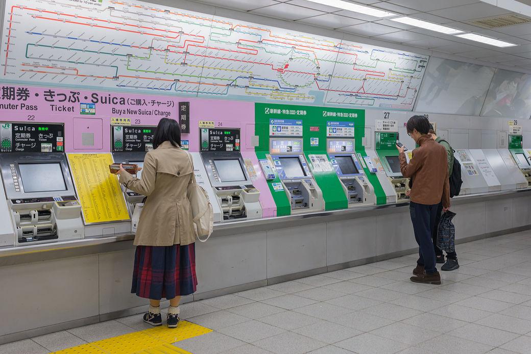 Chico y chica sacando tarjeta de transporte en Japón en la máquina expendedora