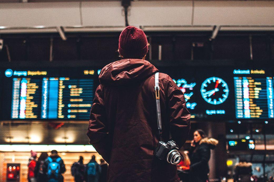 Chico delante paneles de vuelos en aeropuerto