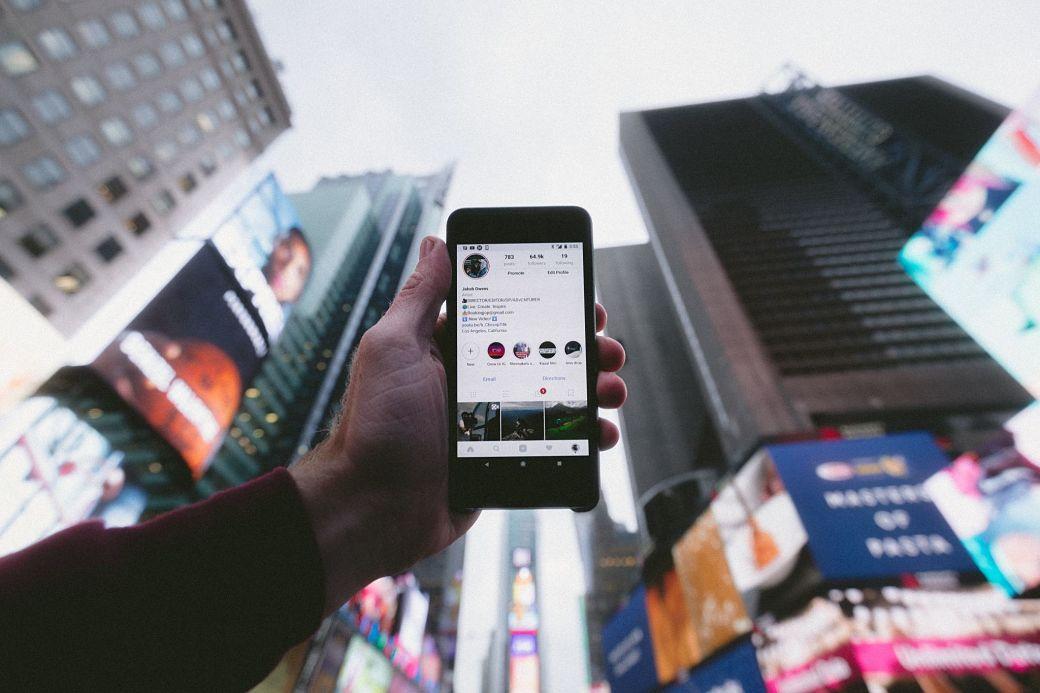 Persona usando el móvil en una gran ciudad