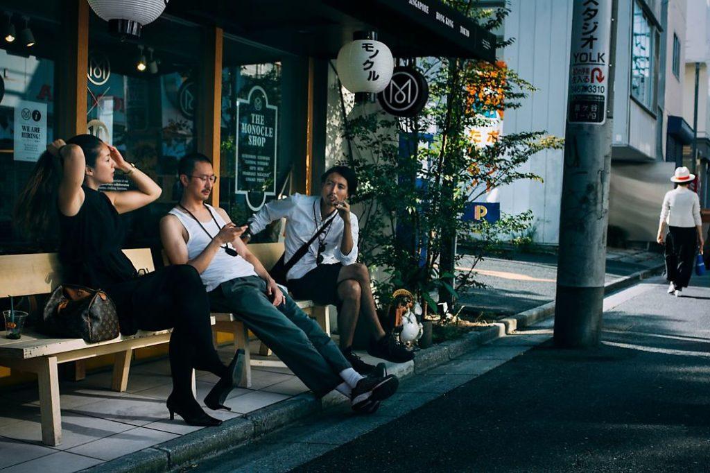 Japoneses esperando sentados delante de un comercio