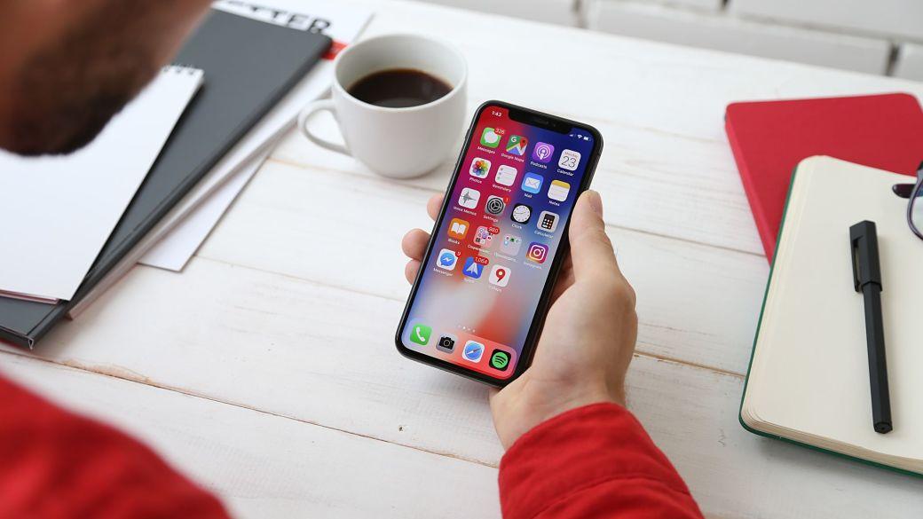 Chico usando el móvil mientras trabaja o estudia