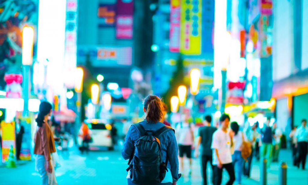 Chica extranjera paseando por una calle en Japón con mochila en la espalda
