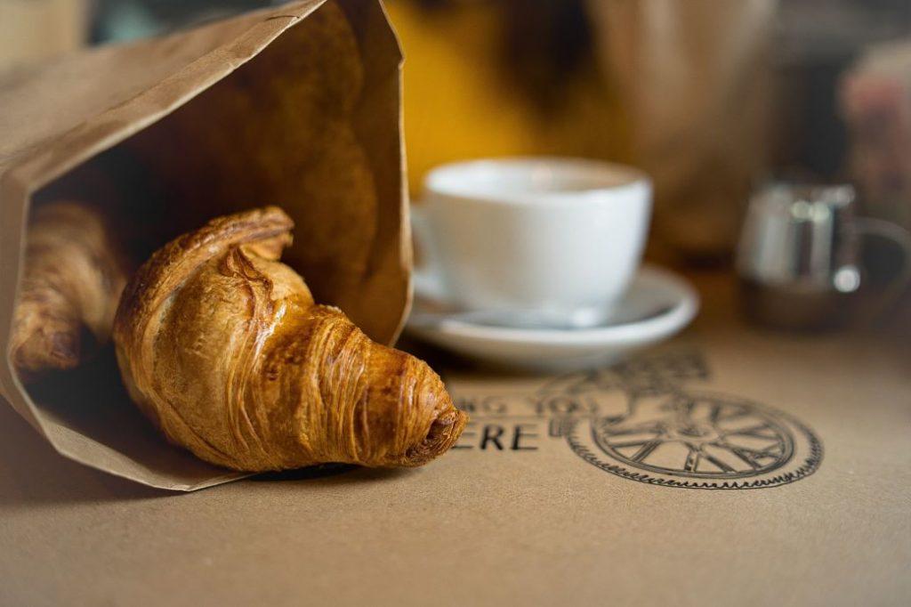 Croissant junto a una taza de café con leche