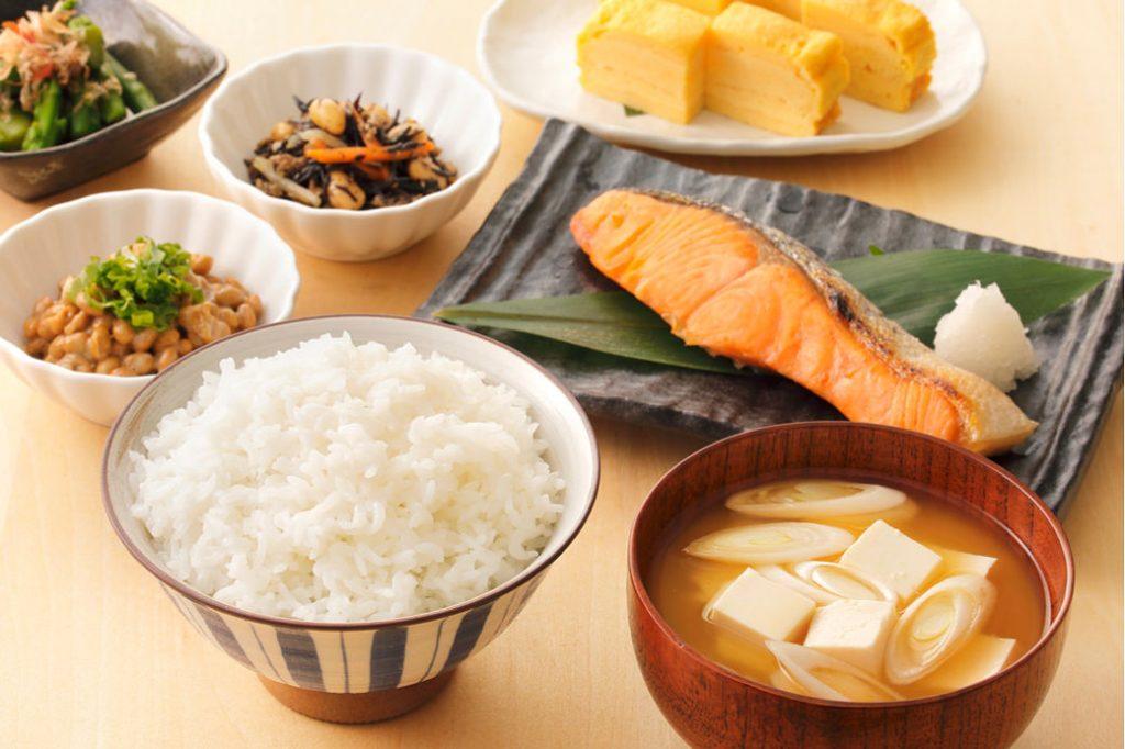 Desayuno japonés tradicional con sopa de miso, arroz, salmón a la plancha, encurtidos, natto y tortilla japonesa