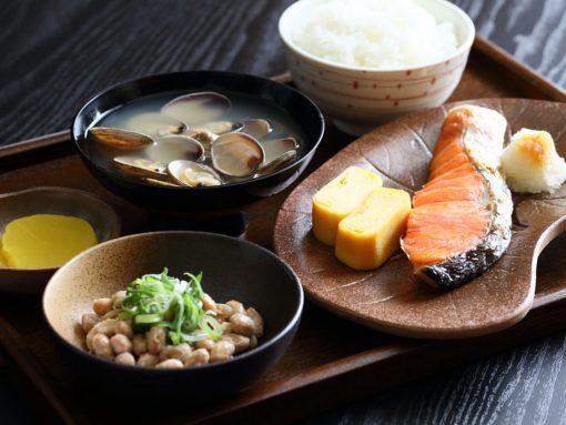 Desayuno tradicional japonés con natto, salmón, arroz y conchas