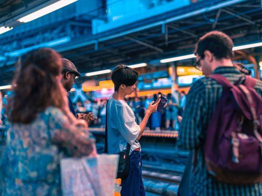 Extranjero junto a otros japoneses esperando al tren en el andén
