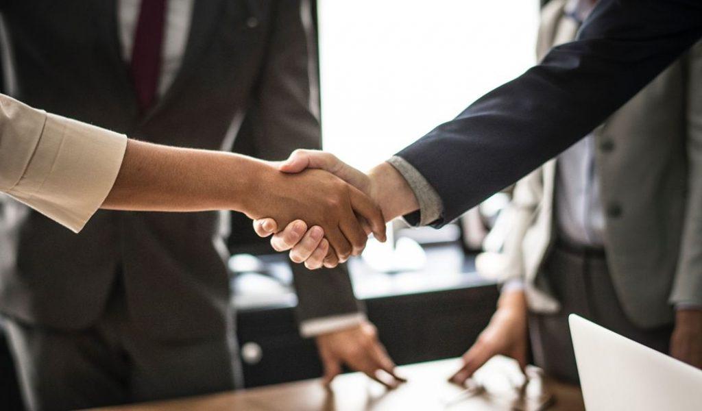 Dos personas se saludan dándose la mano entorne de trabajo