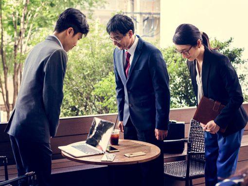 DOs hombres y una mujer japonesa se saludan en ambiente de trabajo