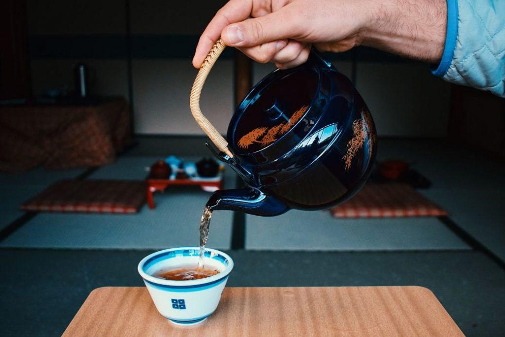 Mano sirviendo taza de té