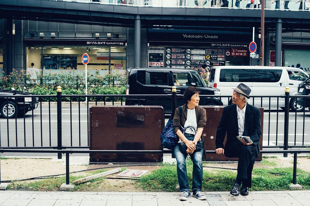 Mujer y hombre de avanzada edad sentados en un banco de un parque en Japón