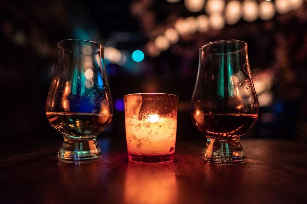 Vasos de whisky junto a una vela