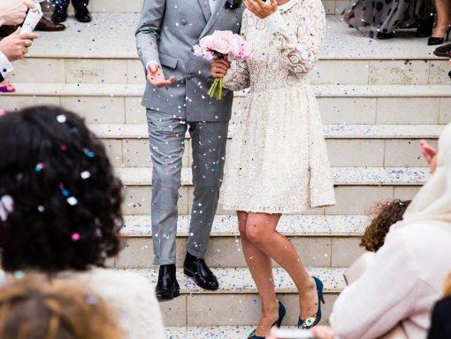 Foto pareja recién casado bajando escaleras con gente vitoreando
