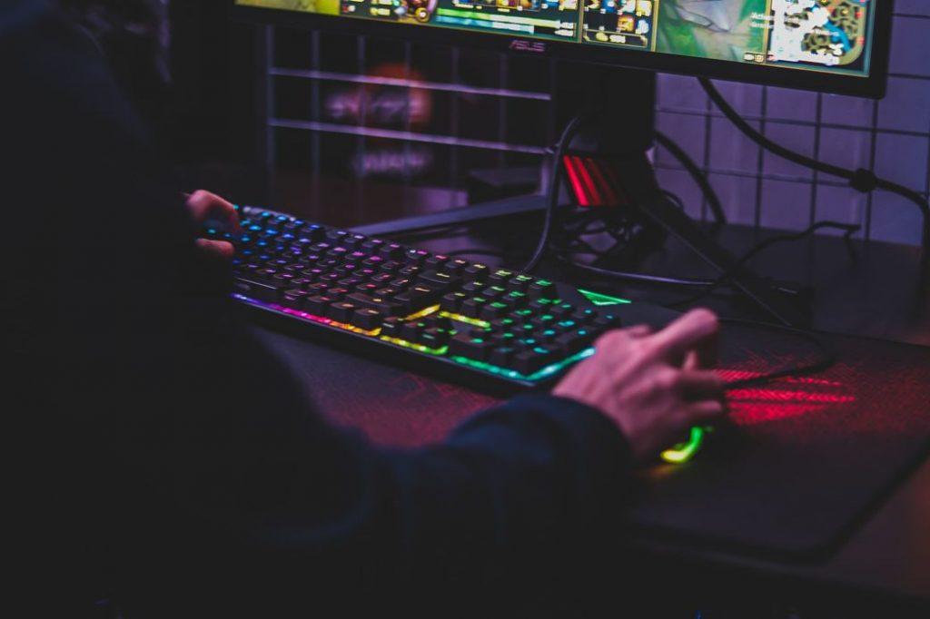 Chico jugando al ordenador a oscuras