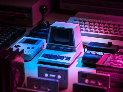 Pequeña computadora, gameboy y casetes en una mesa con luz tenue
