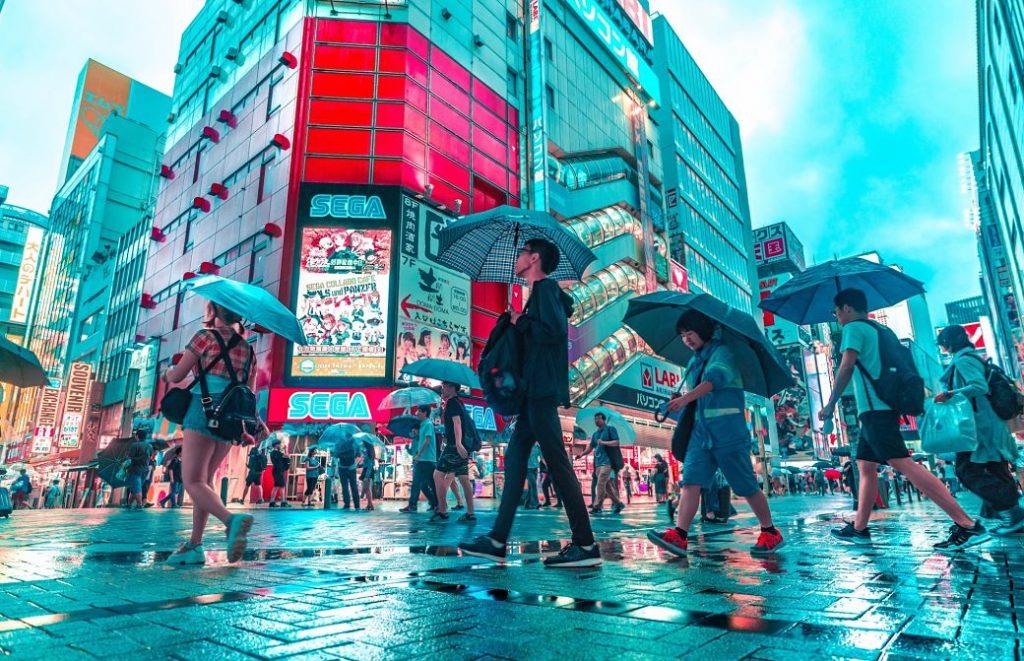 Japoneses paseando bajo la lluvia con pantallas y nones de fondo