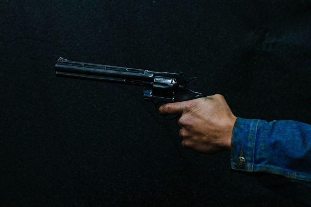 Mano sujetando pistola con fondo negro