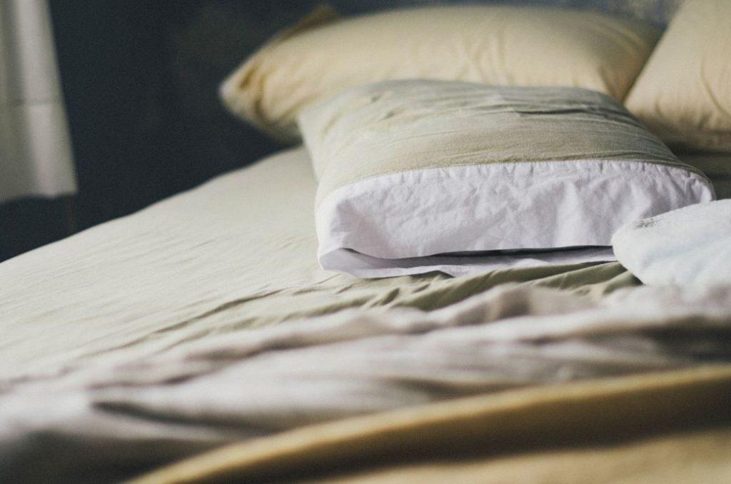 Almohada de color blanco encima de una cama