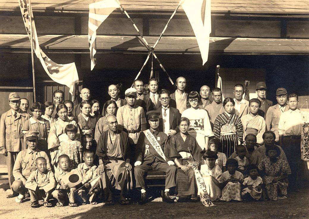 Hombres de la armada imperial junto a la bandera de Japón