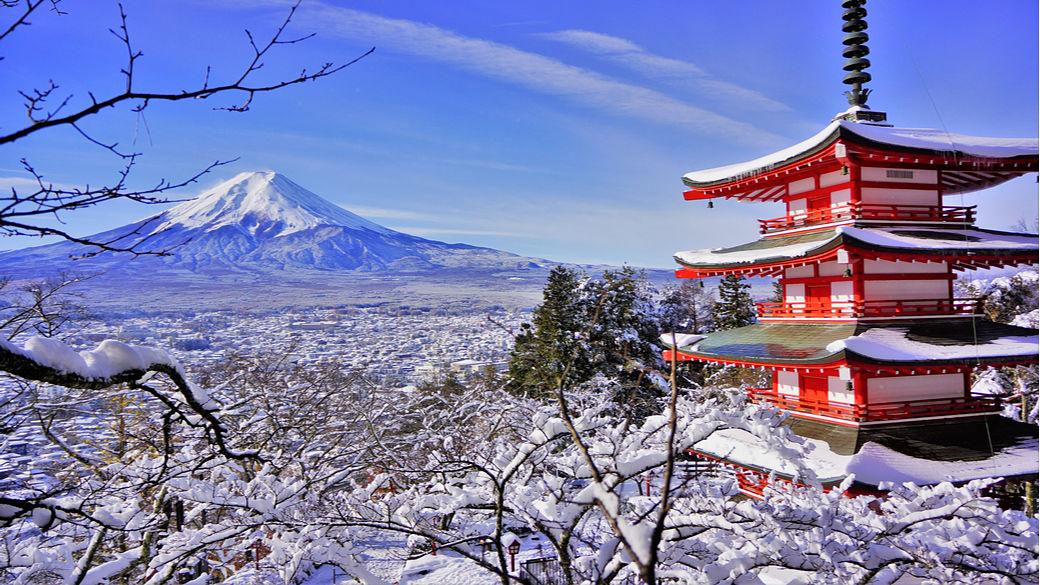 Paisaje nevado de una pagoda y el Monte Fuji a lo lejos