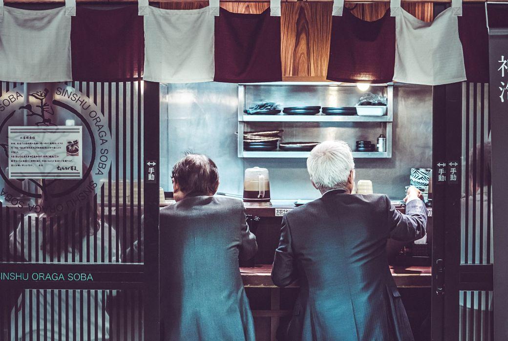 Personas comiendo en la barra de un restaurante japonés