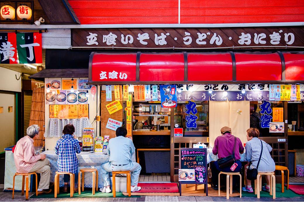 Japoneses sentados comiendo en un restaurante de soba, udon y onigiri de Sendai